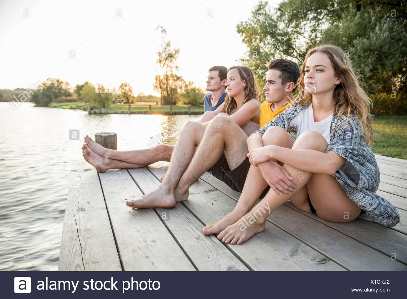 Gruppo di amici seduti sul molo, rilassante Immagini Stock