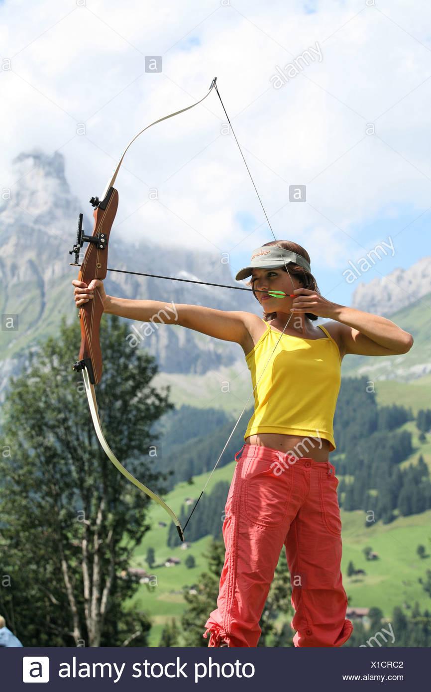 Tiro con l'arco al di fuori delle curve di avvistamento freccia donna arma di arma da fuoco di armi sport sport di precisione shooter archer bow Immagini Stock