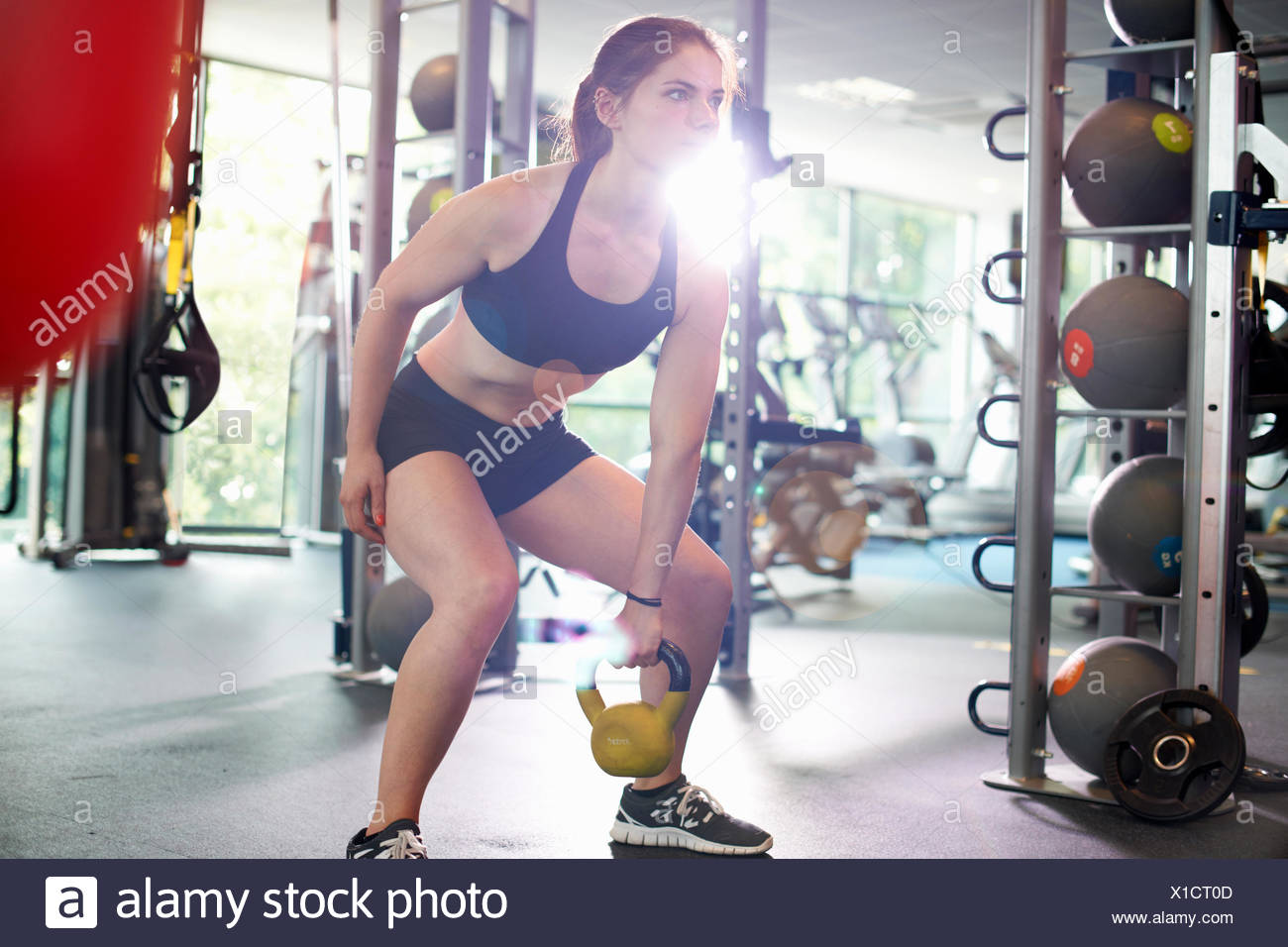 Giovane donna kettlebell di sollevamento Immagini Stock