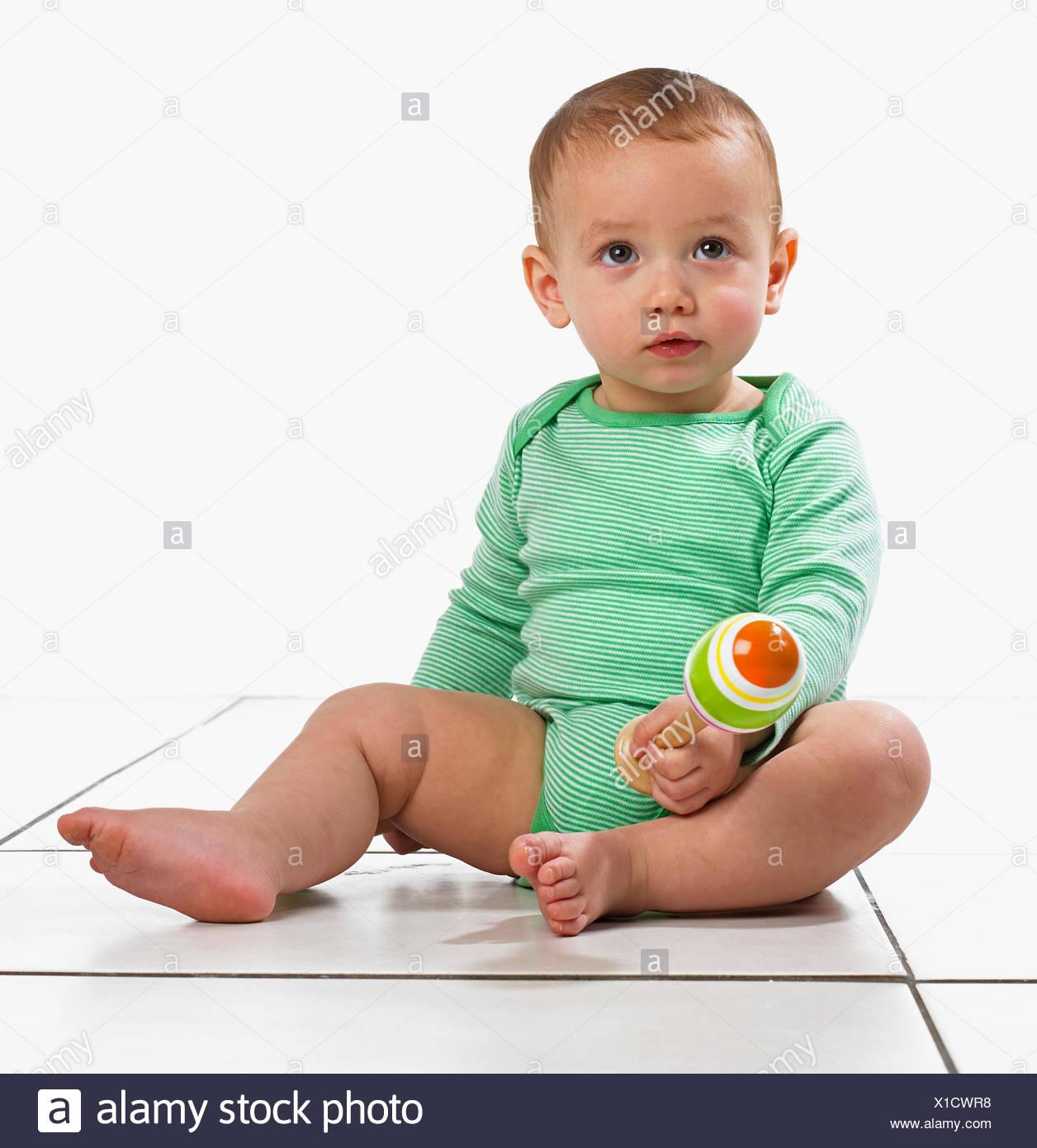 Baby boy (12,5 mesi) seduto a giocare con una maraca Immagini Stock