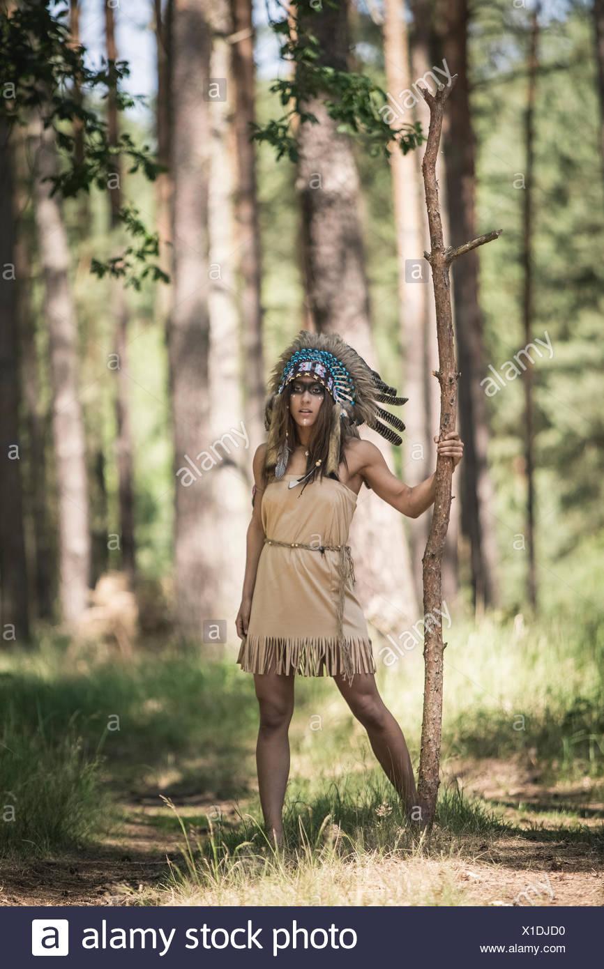 Giovane donna mascherata come un indiano in piedi nel bosco Immagini Stock