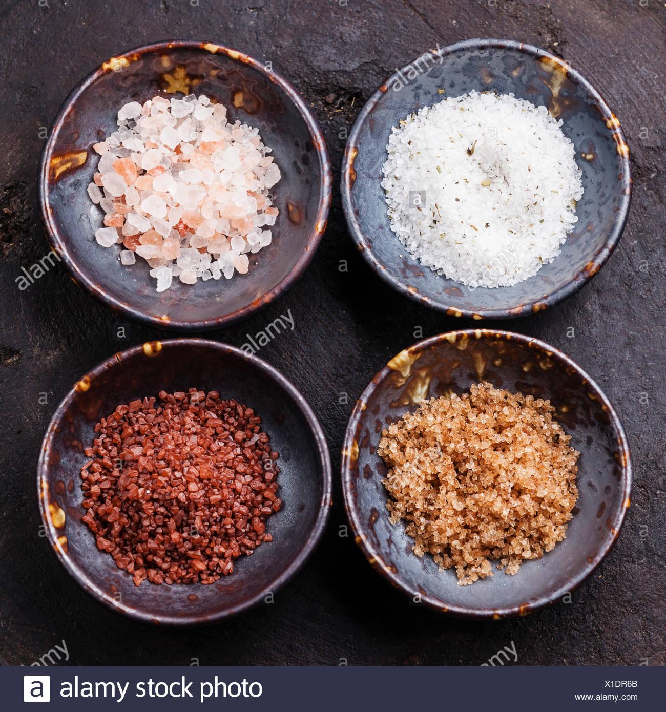 Diversi tipi di alimenti sale grosso in ciotole di ceramica su sfondo scuro Immagini Stock