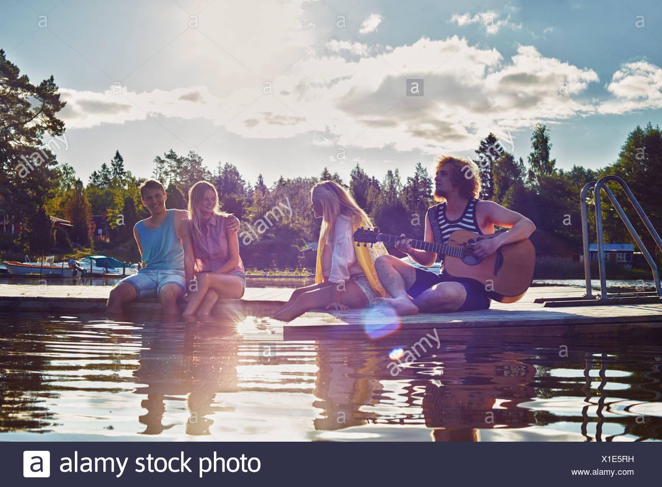 Due giovani coppie relax su Pier, Gavle, Svezia Immagini Stock