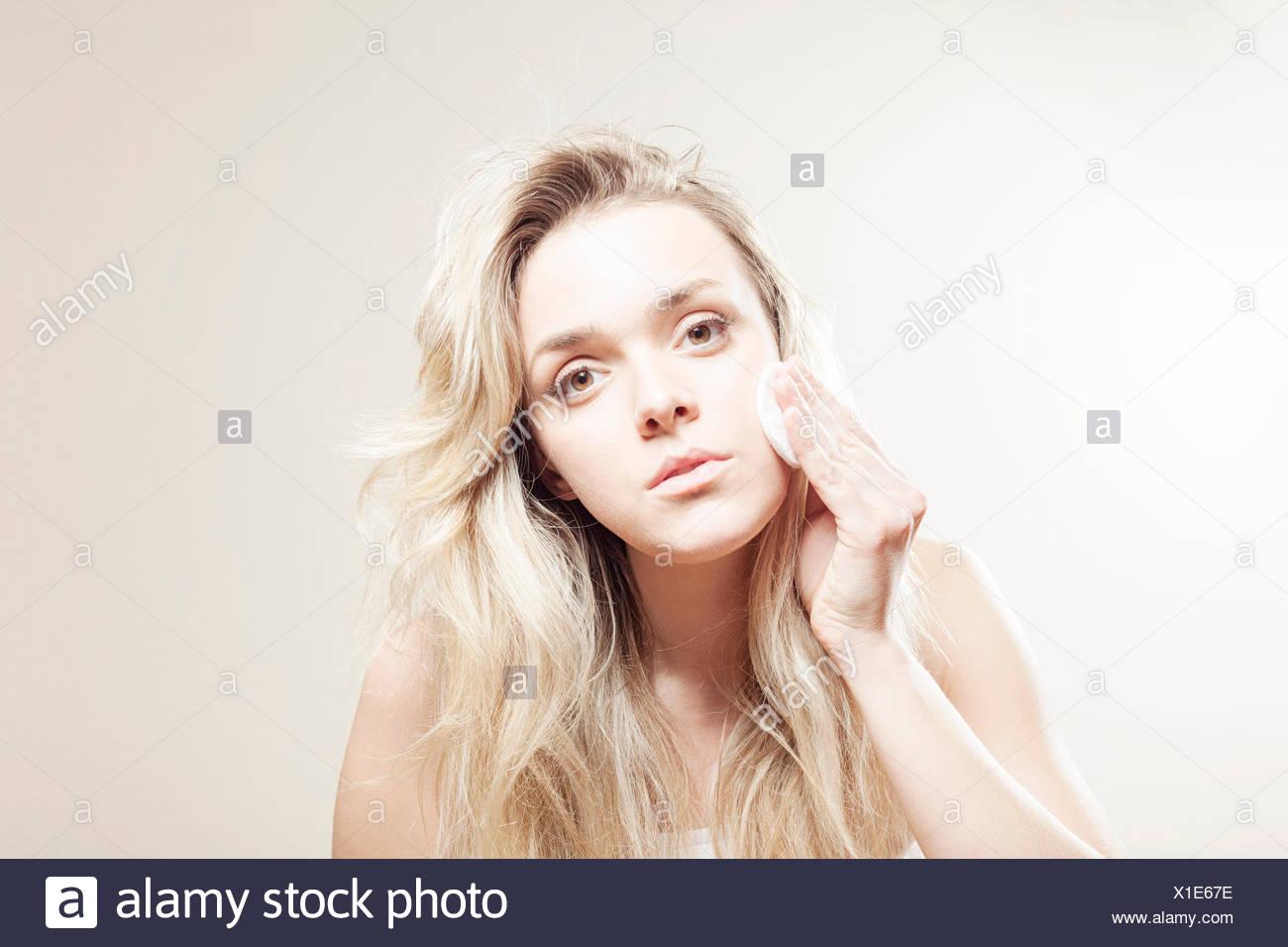 Giovane donna pulizia viso Immagini Stock