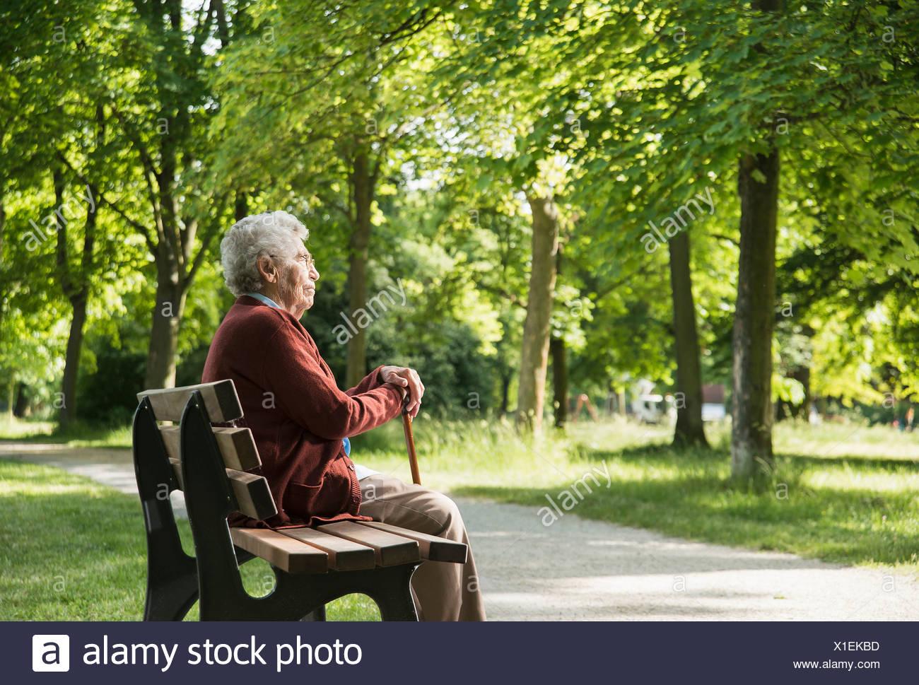 Senior donna seduta su una panchina nel parco Immagini Stock