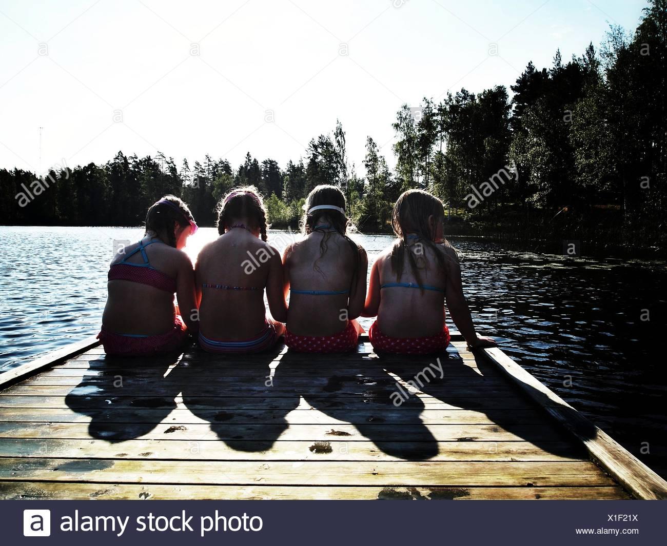La Svezia, vista posteriore di 4 bambini seduti sul molo (6-7 anni, 8-9 anni) Immagini Stock