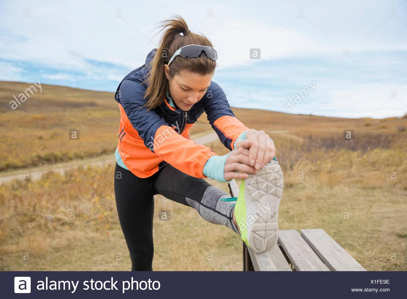 Runner allungamento della gamba sul banco rurale Immagini Stock