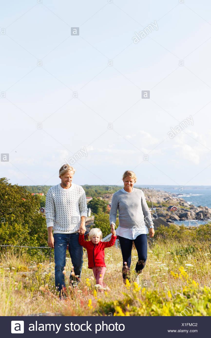 La Svezia, arcipelago di Stoccolma, Sodermanland, Oja, donna e uomo a camminare con il figlio (2-3) attraverso il prato con il mare sullo sfondo Foto Stock