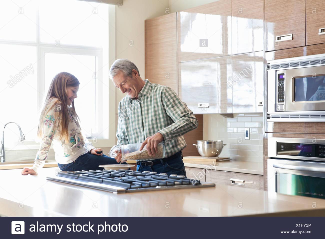 Nonno prepara la colazione per il nipote in cucina Immagini Stock