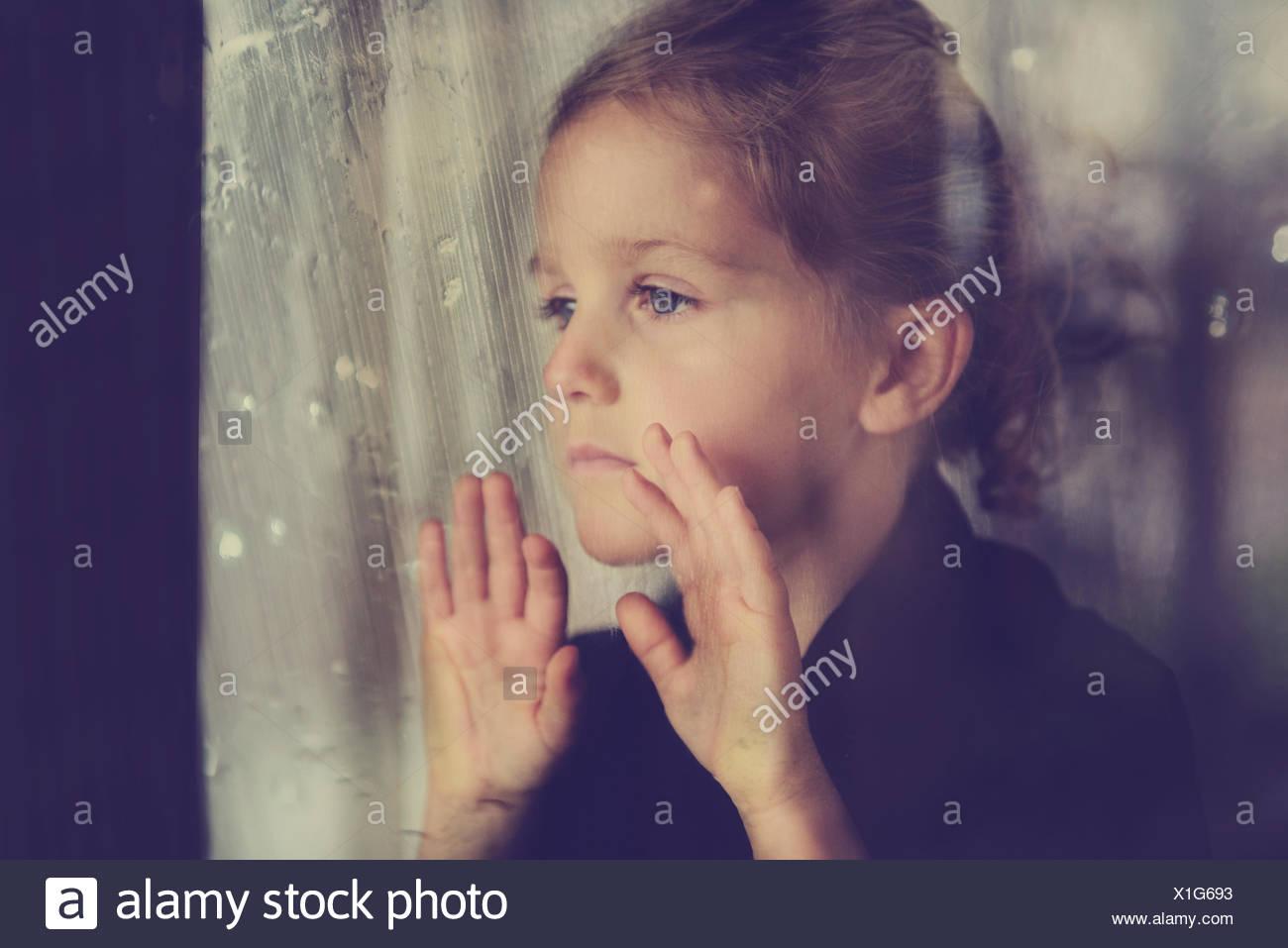 La ragazza (4-5) guardando attraverso la finestra umido Immagini Stock
