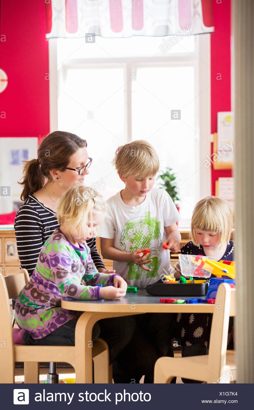 La Svezia, bambini che giocano con insegnante in una scuola materna Immagini Stock