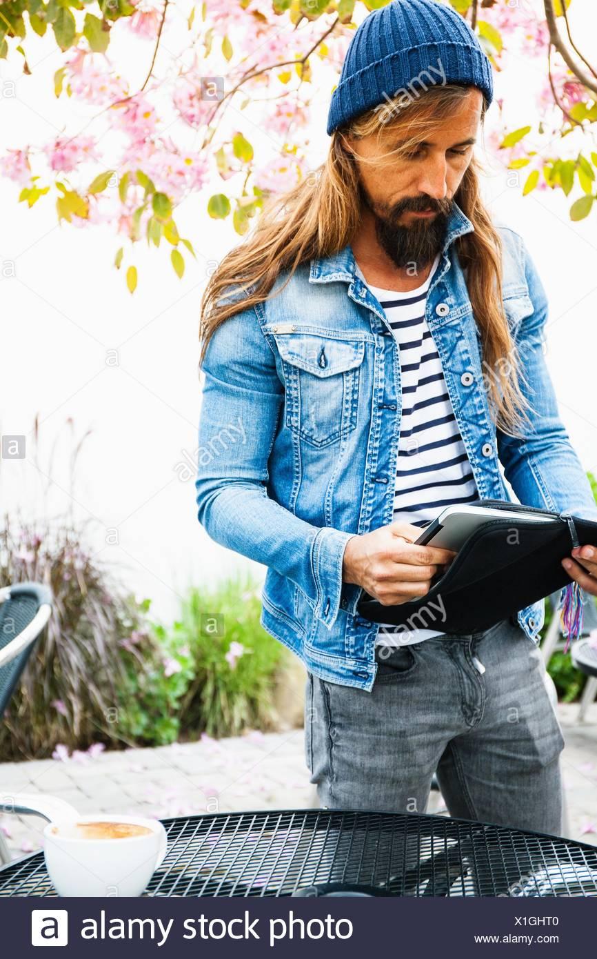 Metà uomo adulto mettendo laptop in caso Immagini Stock