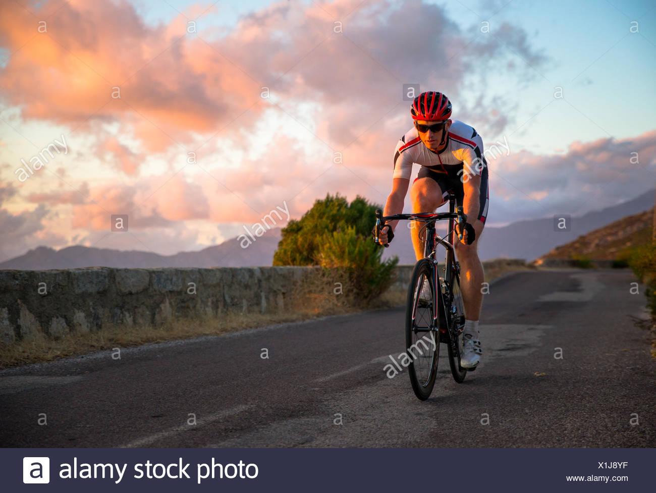 Uomo in bicicletta al tramonto, Corsica, Francia Immagini Stock