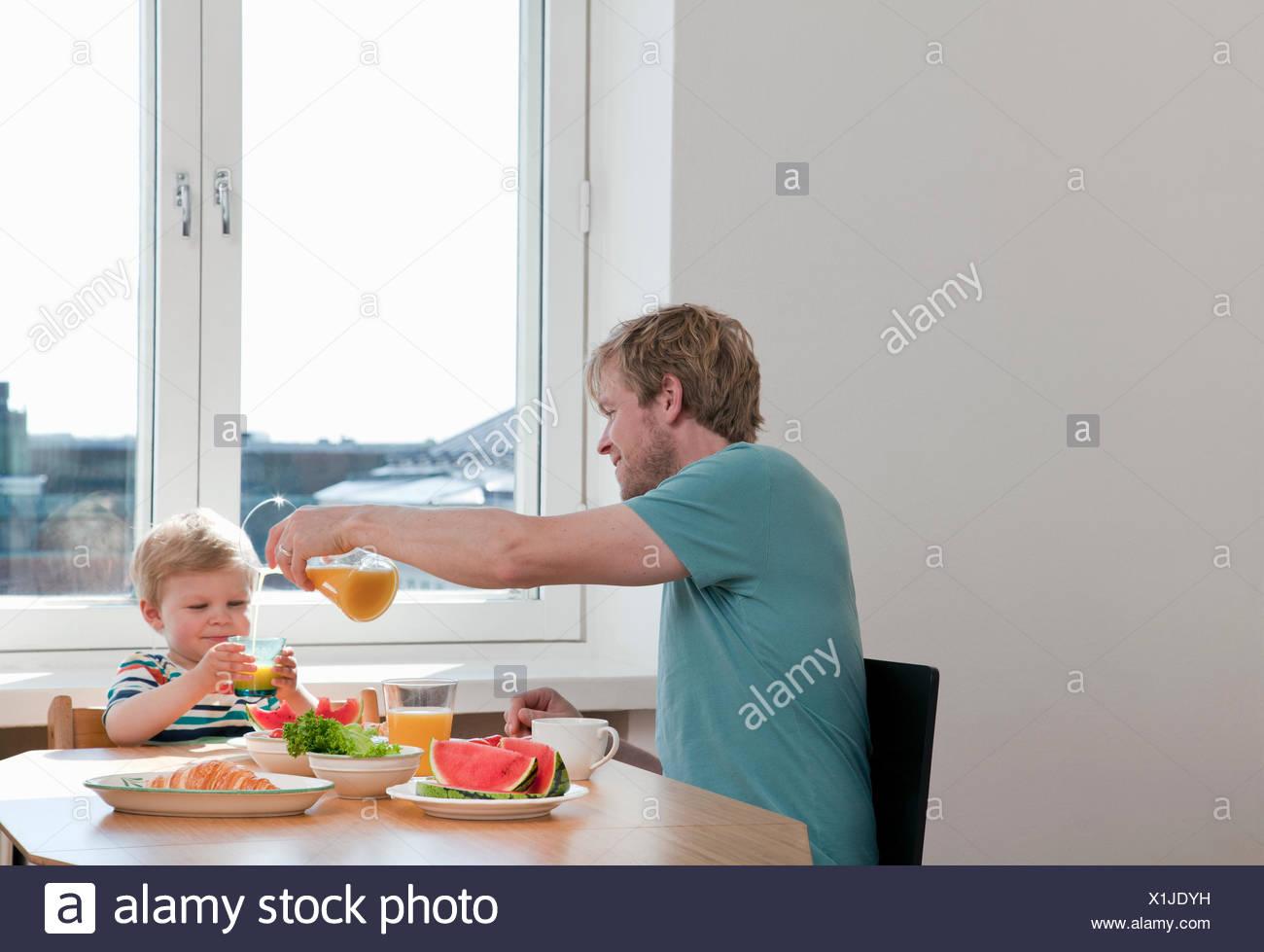 Padre e figlio toddler avente prima colazione al tavolo della cucina Immagini Stock