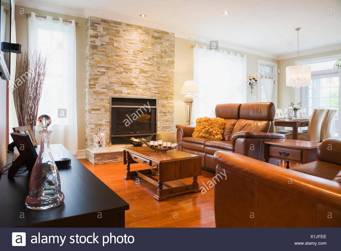 Divani in pelle marrone con tavolo da caffè in legno e caminetto in