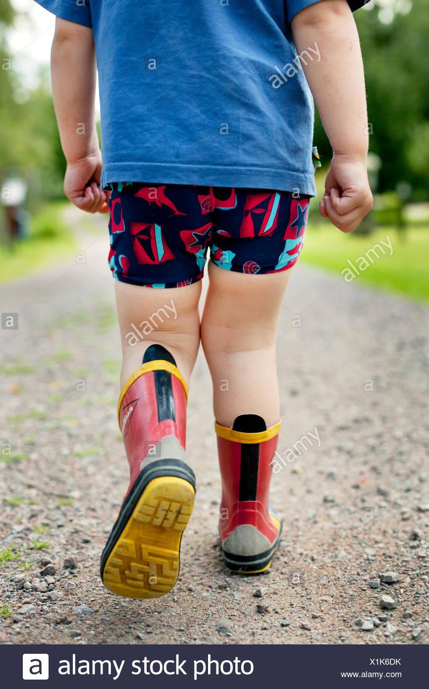 La Svezia, Little Boy (2-3) passeggiate in stivali di gomma Immagini Stock