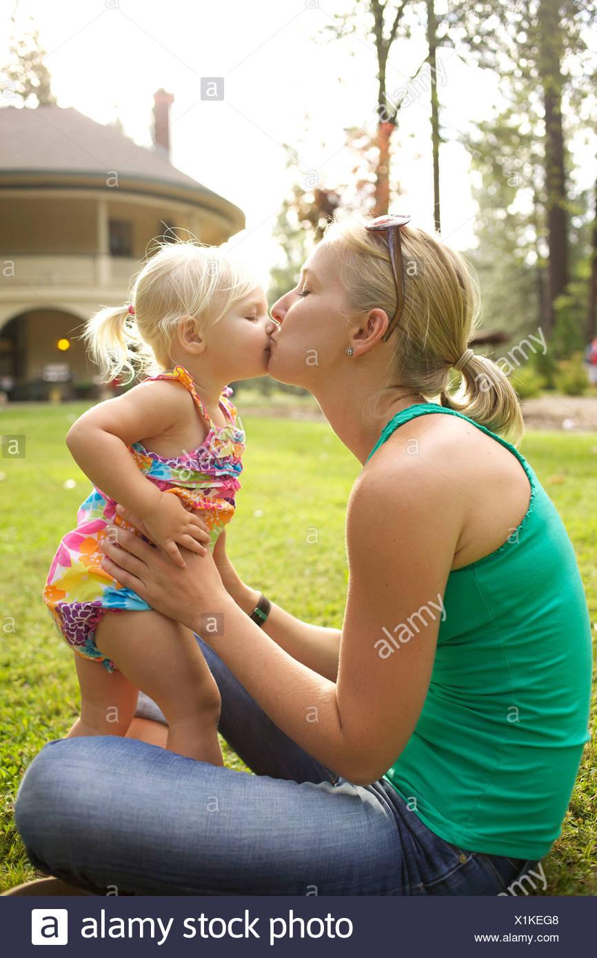 Una madre bacia la sua bambina. Immagini Stock