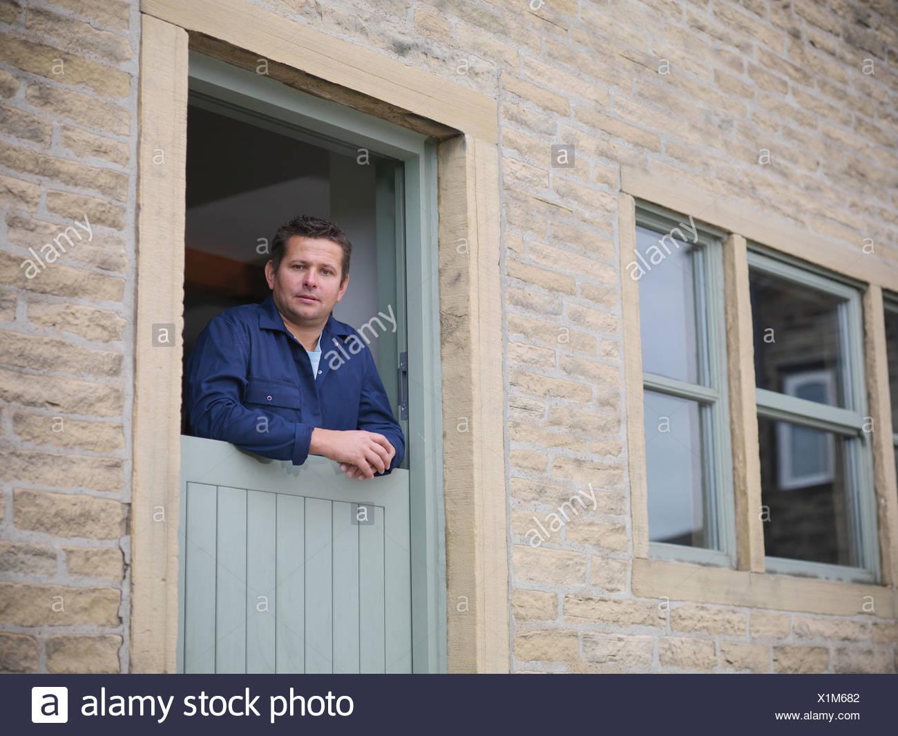 Ritratto di agricoltore guardando fuori dalla porta di casa colonica Immagini Stock