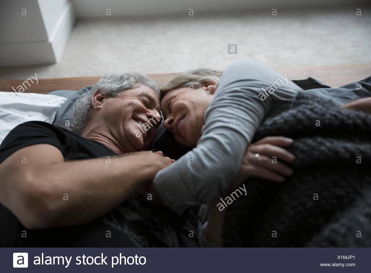 Affettuoso,romantico coppia senior coccole a letto Immagini Stock