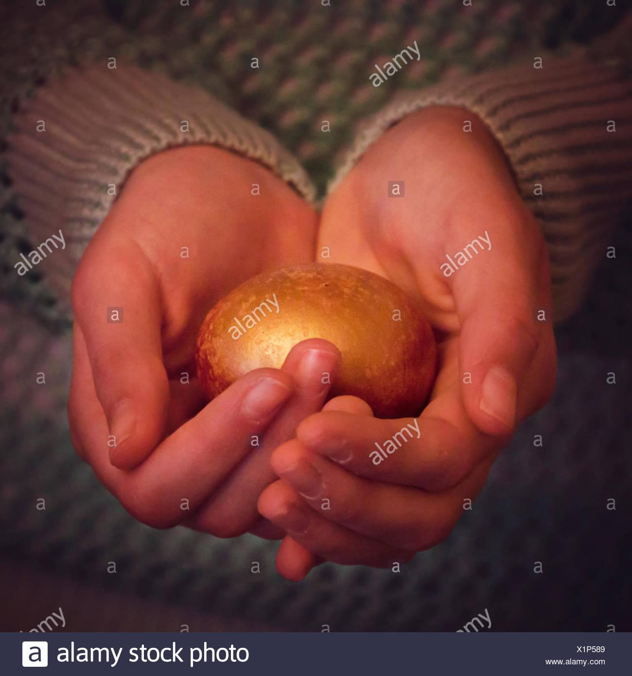 Una ragazza con golden nest egg nelle sue mani Immagini Stock