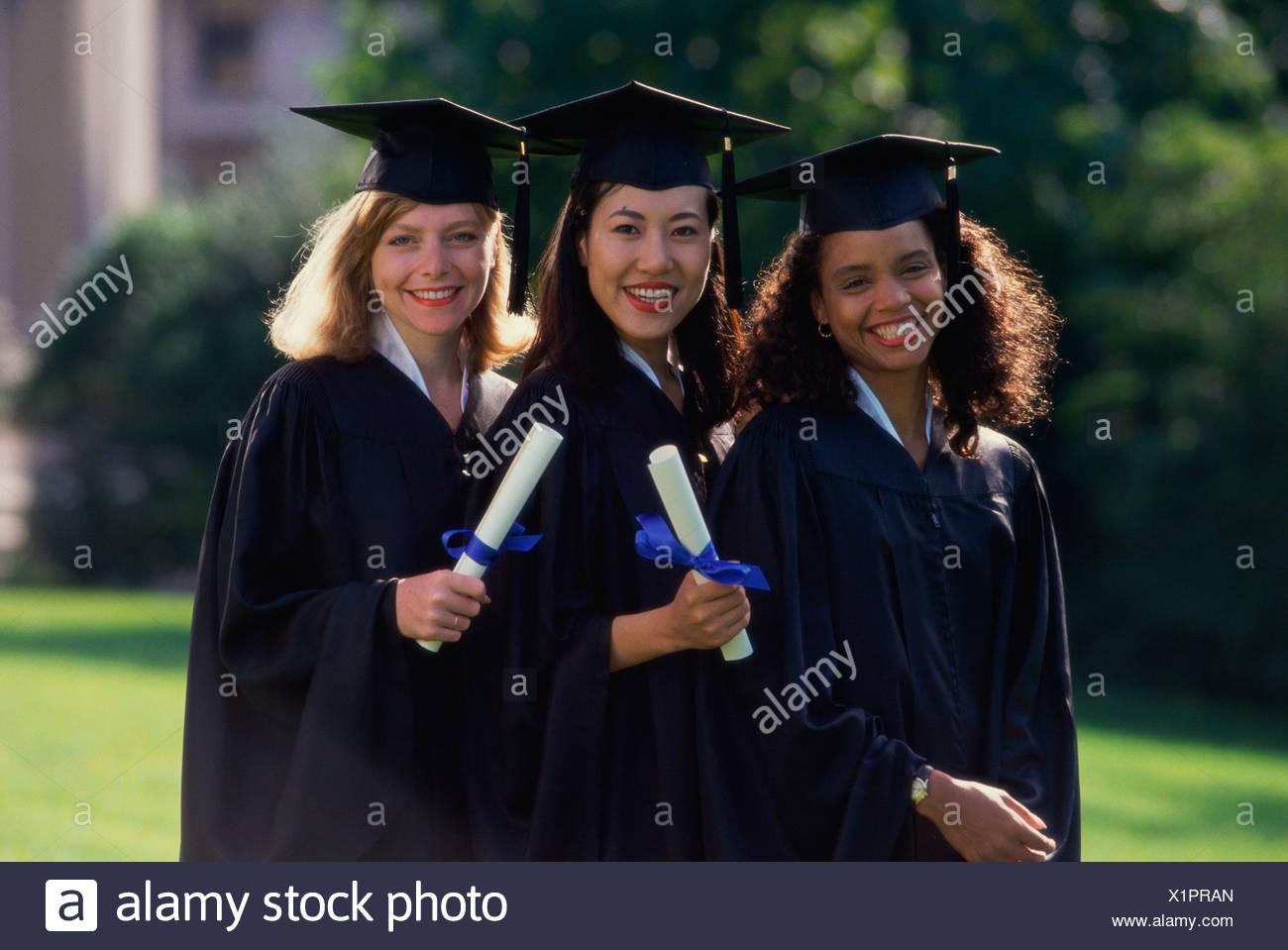 Tre giovani donne che indossano abiti di laurea e diplomi di contenimento 9bf1f27570b6