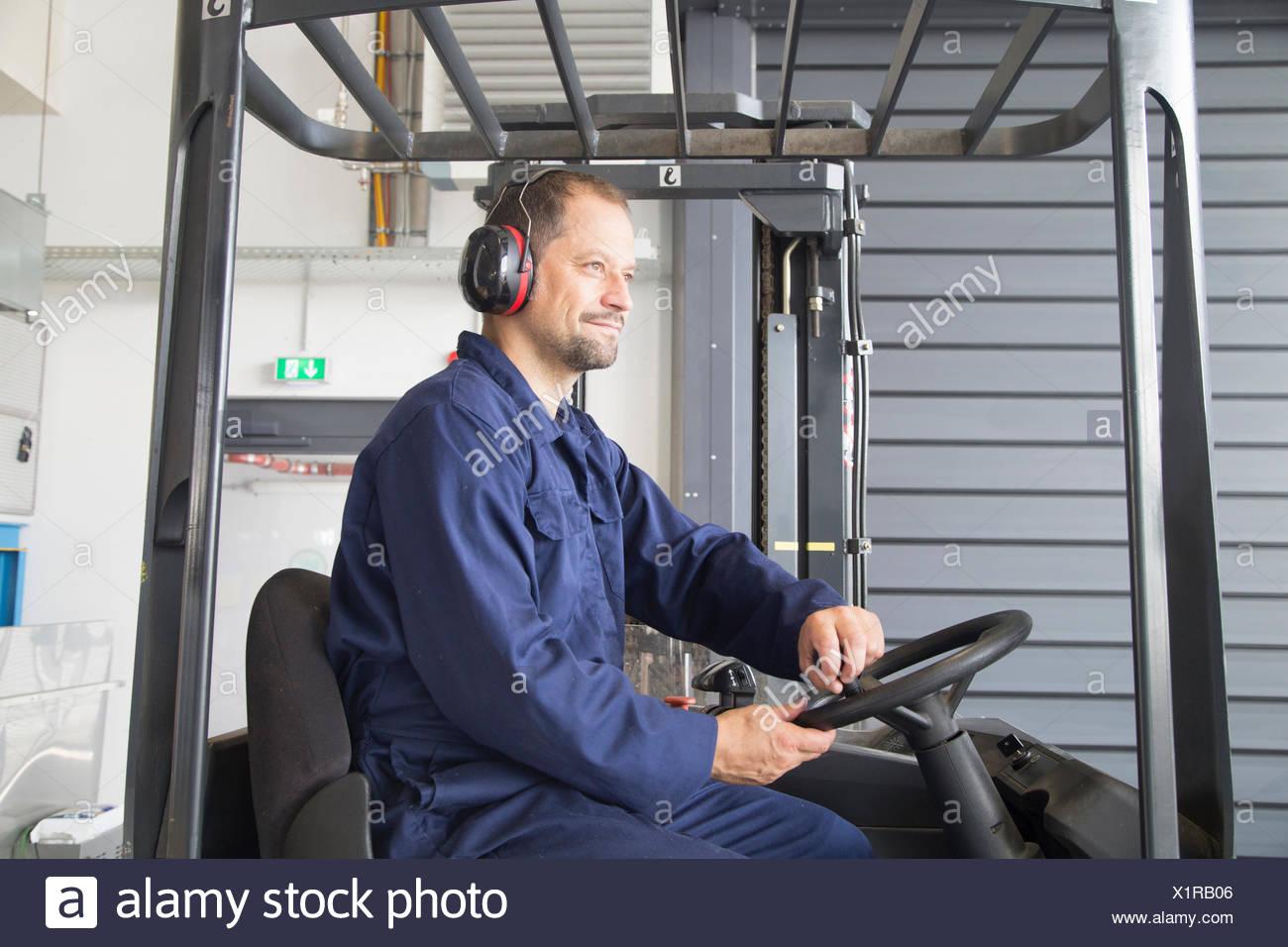 Lavoratore nel carrello elevatore a forche in impianto industriale Immagini Stock