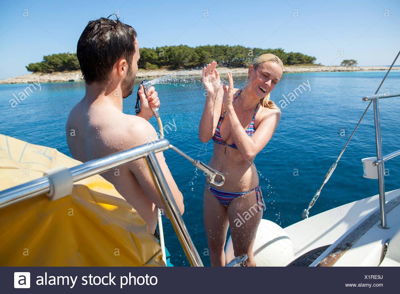 La donna che viene spruzzato con acqua sulla barca a vela mare Adriatico Immagini Stock