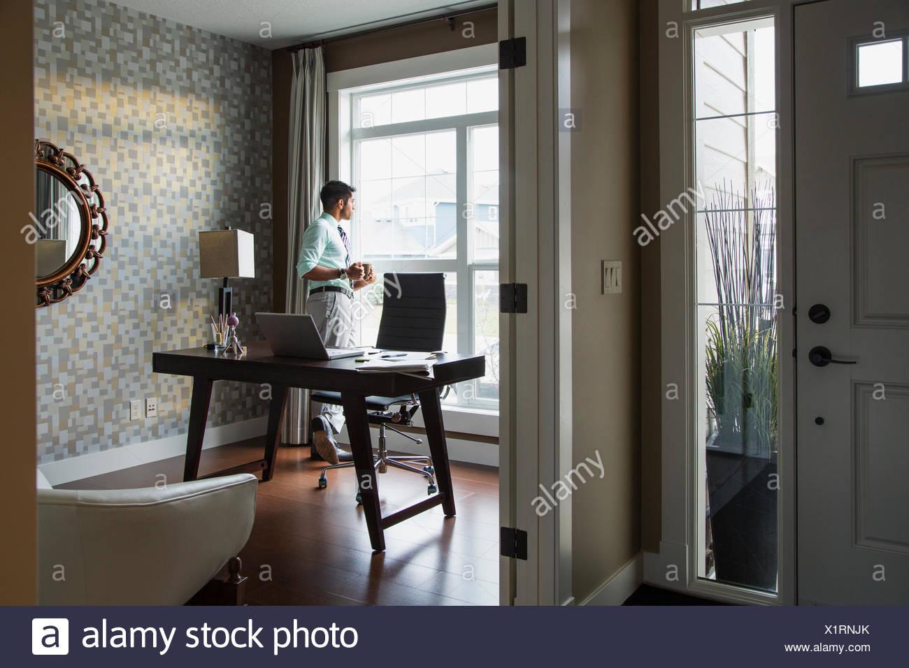 Uomo di bere il caffè a casa Finestra di ufficio Immagini Stock