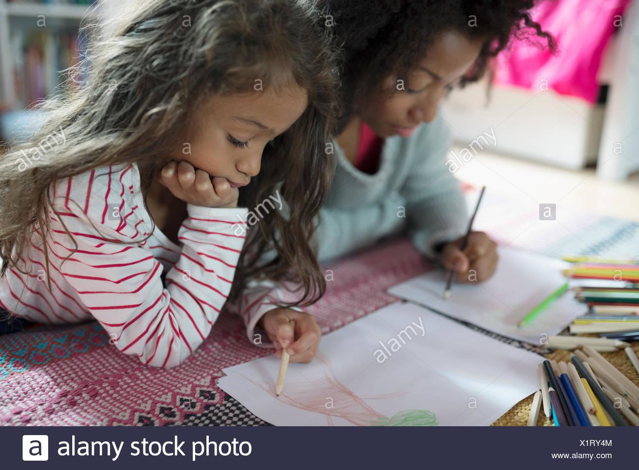 Madre e figlia di Disegno con matite colorate su rug Immagini Stock