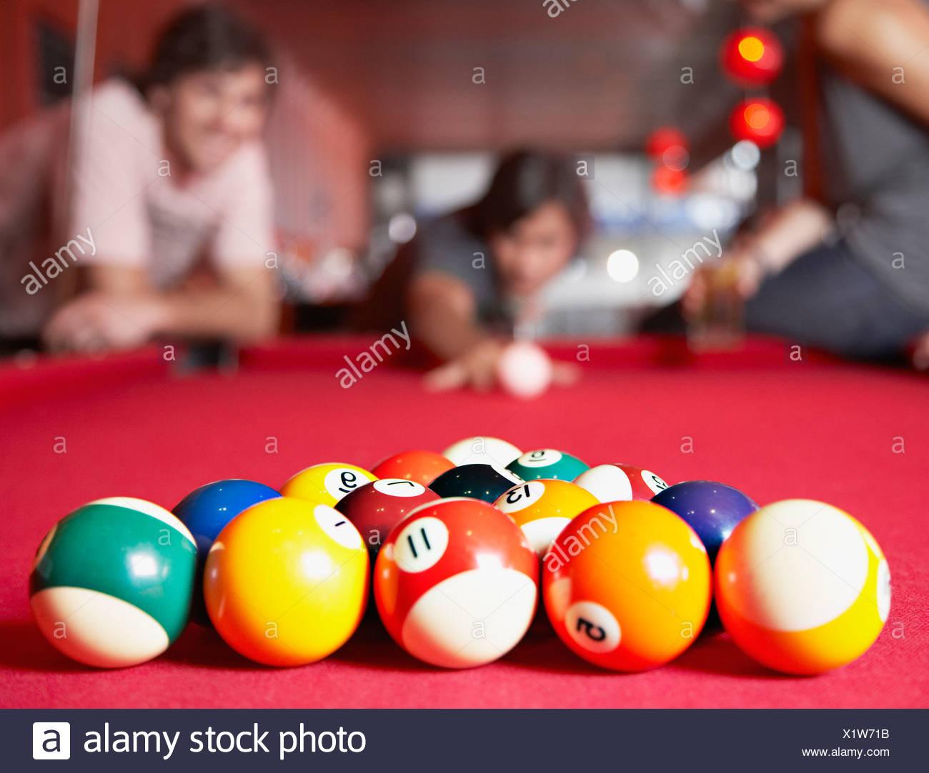 Tre persone a giocare in piscina sulla focalizzazione delle palle di biliardo Immagini Stock