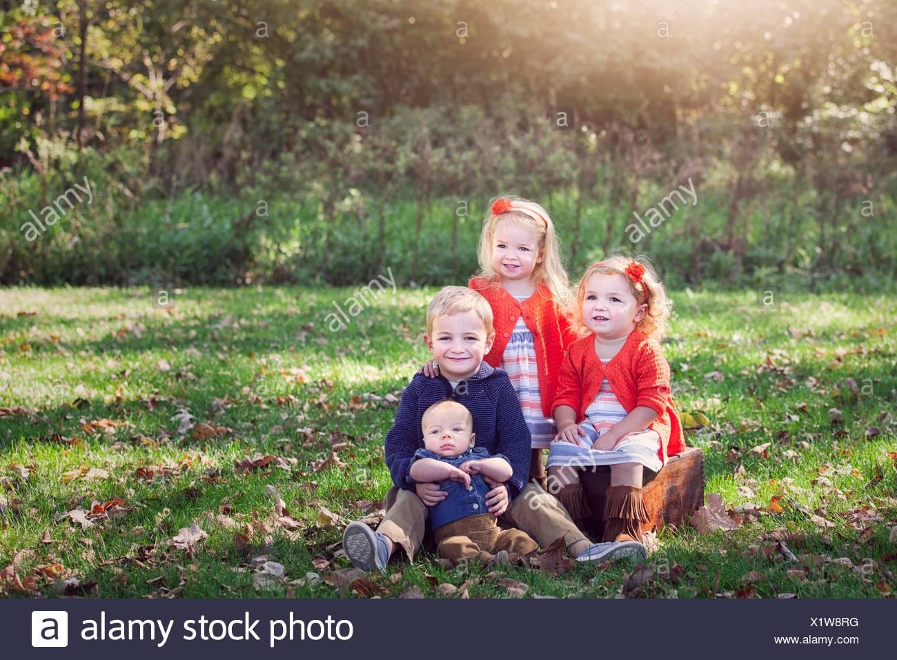 Quattro bambini famiglia su foglie di autunno ricoperto di erba che posano per una foto sorridente Immagini Stock