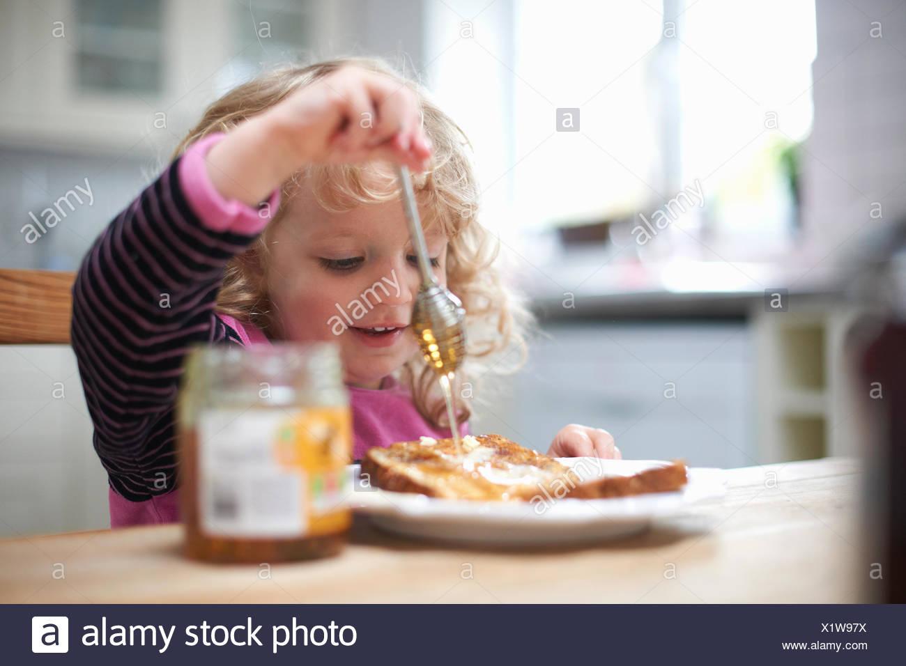 Giovane ragazza seduta al tavolo della cucina, drizzling miele su pane tostato Immagini Stock
