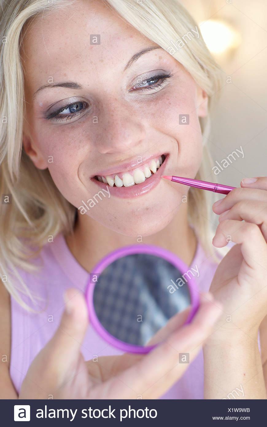 Femmina lunghi capelli biondi sciolti usurati che indossa un color malva  vest tenendo un piccolo giro viola bordata mirrand mano una rosa luminoso 35eaf54280e