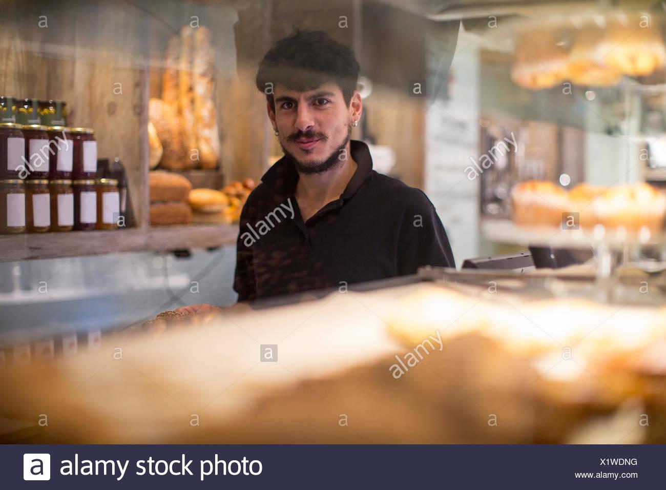Ritratto di giovane maschio barista dietro cafe counter Immagini Stock