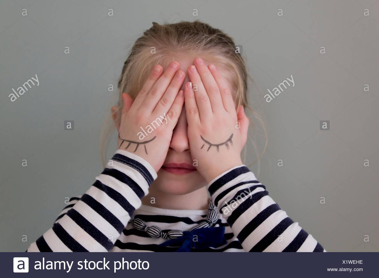 Ragazza che copre la sua gli occhi con le mani che hanno occhi disegnato su di esse Immagini Stock