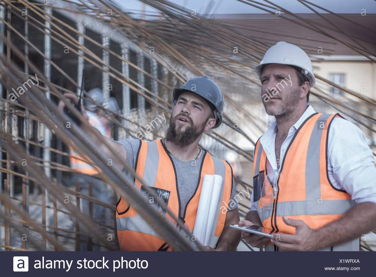Il Site manager e builder a discutere di asta di acciaio strutture sul sito in costruzione Immagini Stock