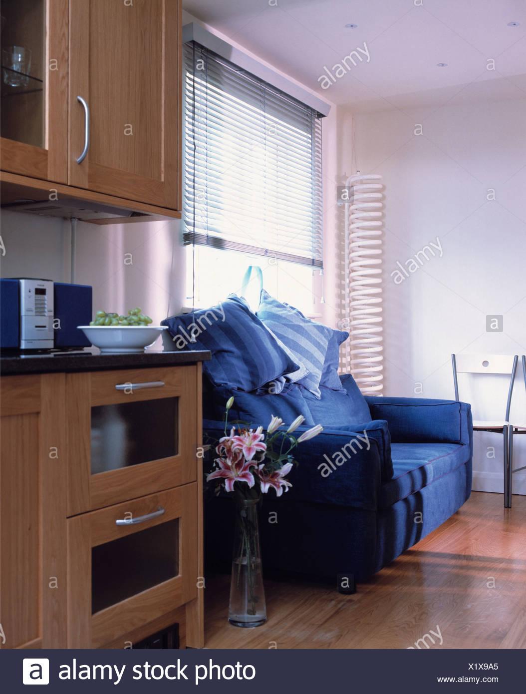 Blu brillante divano sotto la finestra con tenda a veneziana in ...