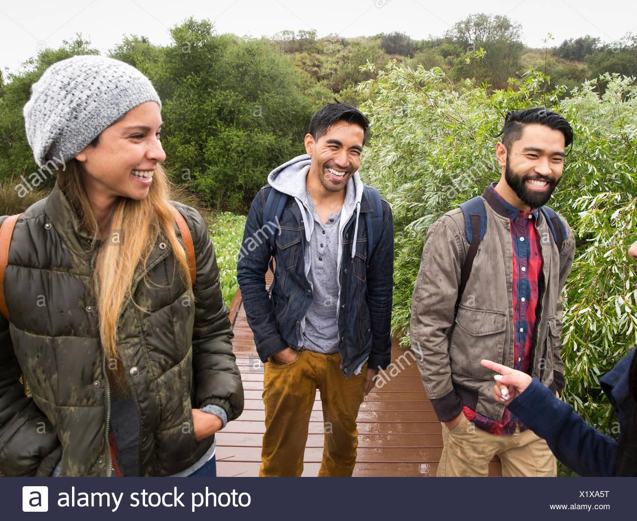Sorridente giovane donna e due giovani uomini a camminare in un parco Immagini Stock
