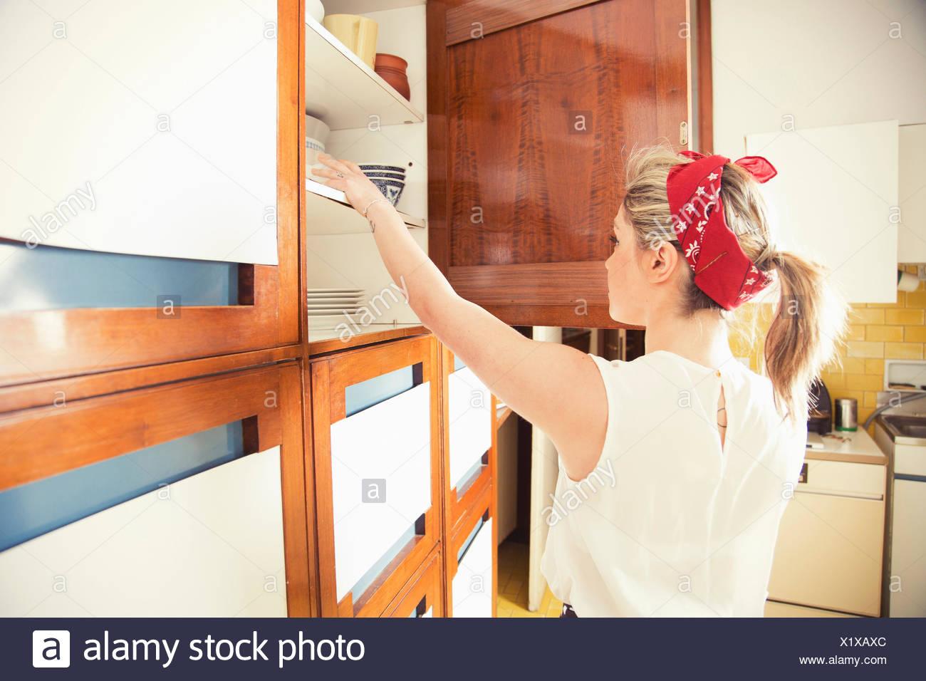 La Credenza Gas : Giovane donna raggiungendo per la credenza in cucina vintage foto