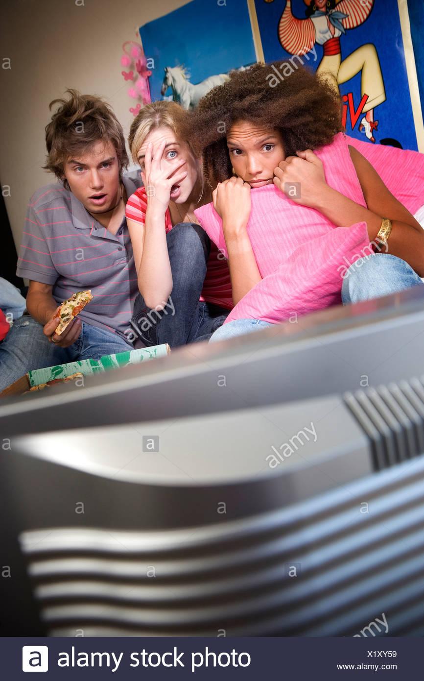 Tre amici adolescenti a guardare la televisione con paura espressioni sulle facce, televisione in primo piano Immagini Stock