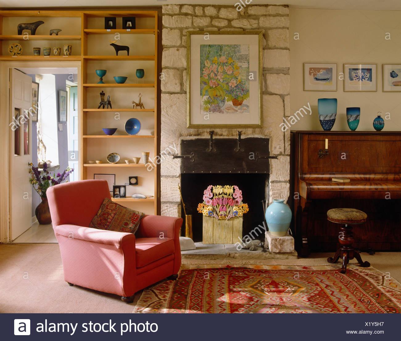Poltrona rosa e parete aperta ripiani in paese soggiorno con ...