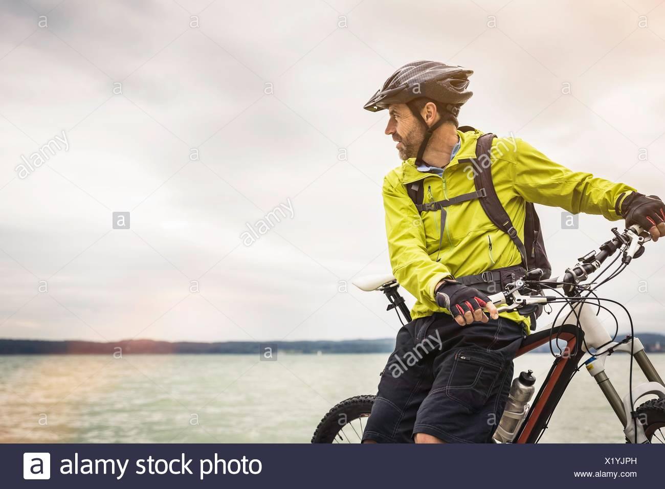 Maschio maturo mountain biker guardando fuori dal lago Immagini Stock