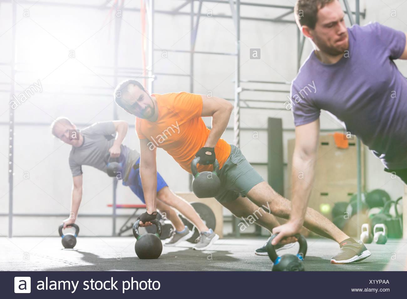 Gli uomini che esercitano con kettlebells crossfit in palestra Immagini Stock