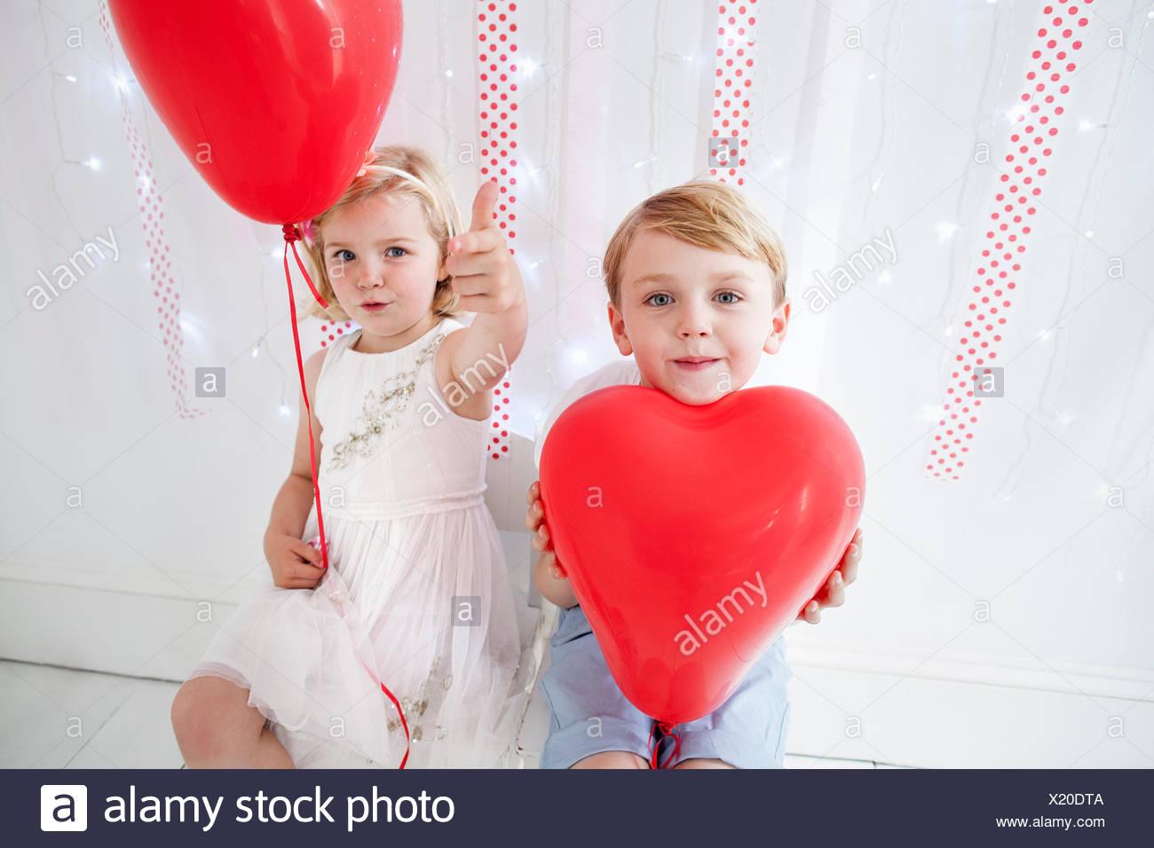 Ragazzo e ragazza in posa per una foto in un studio di fotografi, tenendo palloncini rossi. Immagini Stock