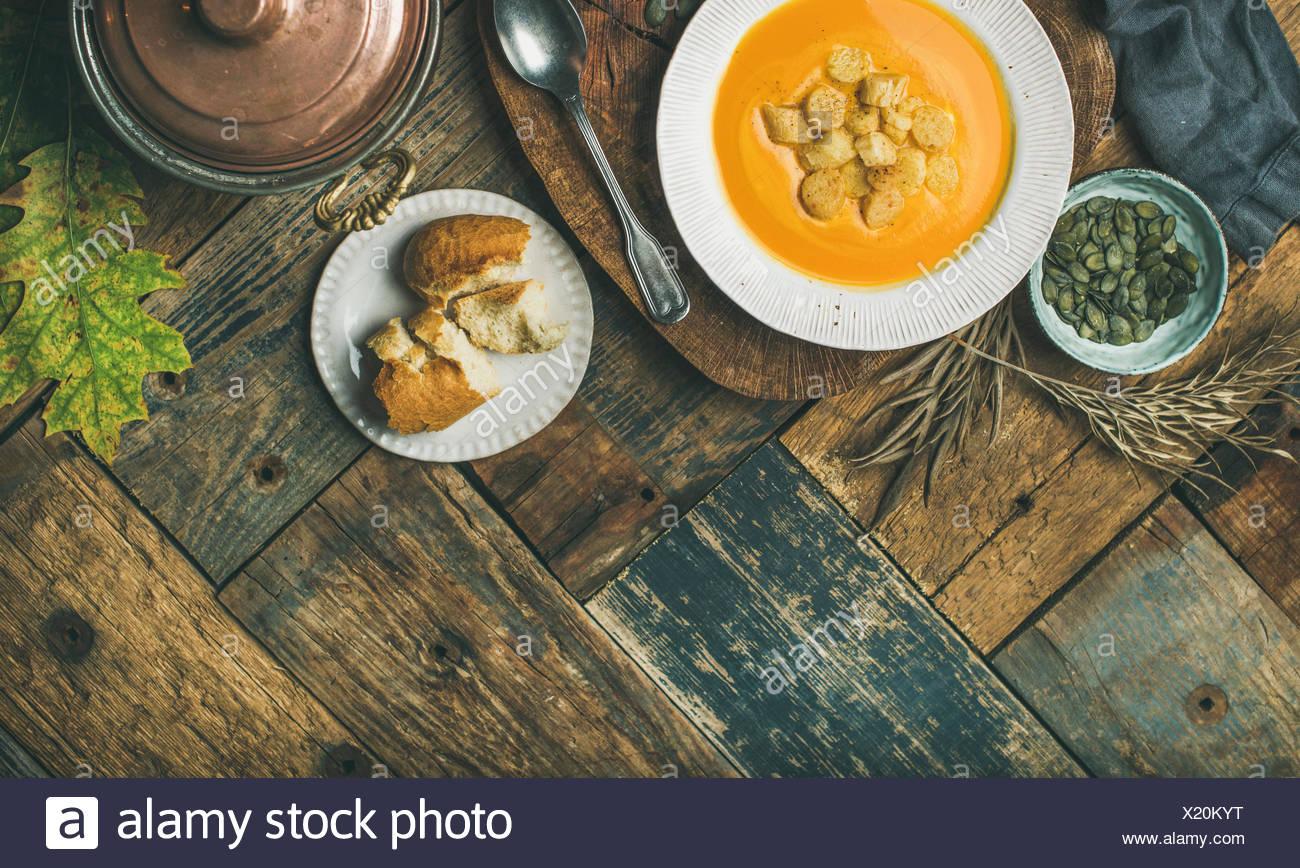 Caduta di riscaldamento Crema di zucca zuppa con crostini e semi sulla scheda sopra in legno rustico sfondo, spazio copia, flat-laici, vista dall'alto. Autunno vegetariano, veg Immagini Stock