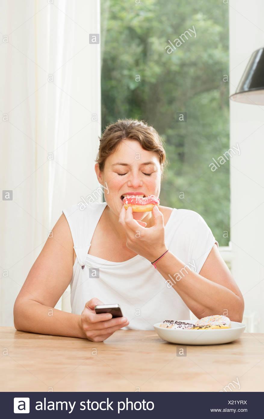 Donna seduta a tavola a mangiare ciambelle e utilizza lo smartphone Immagini Stock