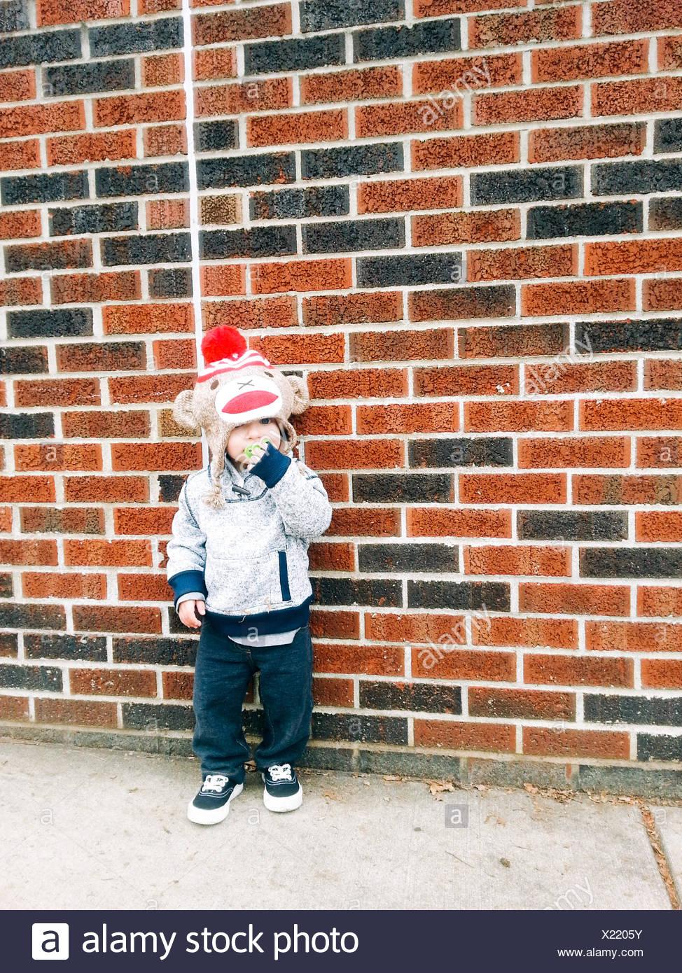 Ragazzo appoggiata contro un muro di mattoni Immagini Stock