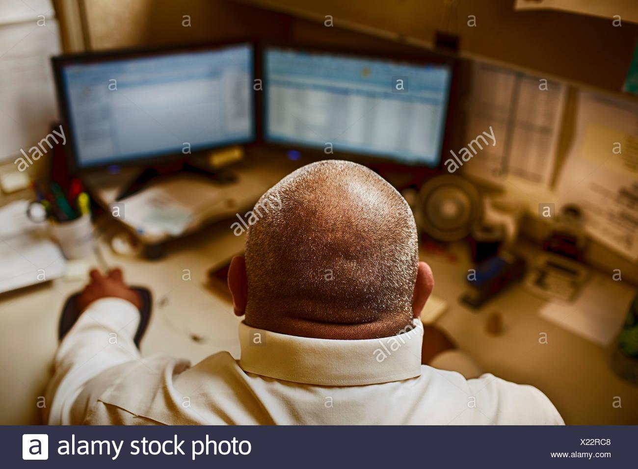 Uomo maturo lavorando nella sala di controllo di un impianto di produzione Immagini Stock