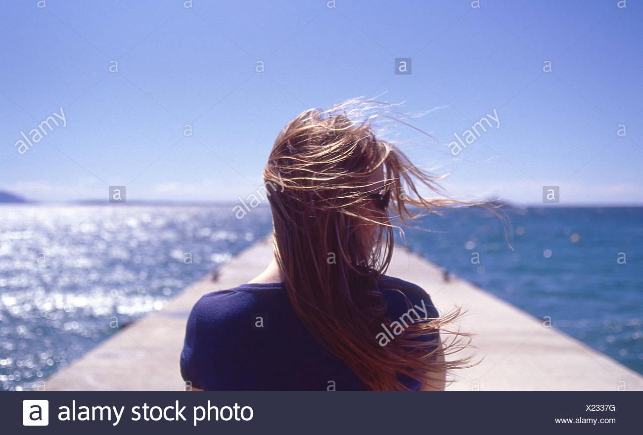 Francia, Juan les Pins, vista posteriore della donna con il vento che soffia Immagini Stock