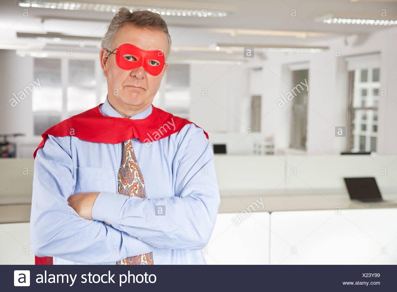 Ritratto di grave imprenditore nel costume da supereroe in office Immagini Stock